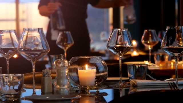 Glasses And Candle On The Table At A Restaurant With A Waiter In The Background Glasses And Candle On The Table At A Restaurant With A Waiter In The Background. wait staff stock videos & royalty-free footage