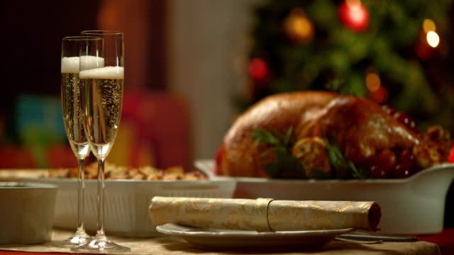 slo mo bicchieri di champagne di natale tabella - christmas table video stock e b–roll