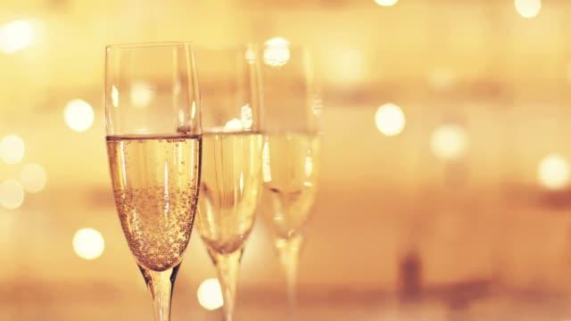 vidéos et rushes de verres de champagne sur fond de bokeh de lumières de clignotant - flûte à champagne