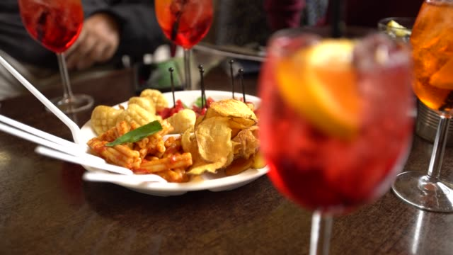 4K, Glasses of sparkling wine with aperol cocktail and appetizer platter 4K, Glasses of sparkling wine with aperol cocktail and appetizer platter with chips fried potatoes and pasta on the table at restaurant. Italian aperitives at outdoor bar in the street of Italy-Dan aperitif stock videos & royalty-free footage