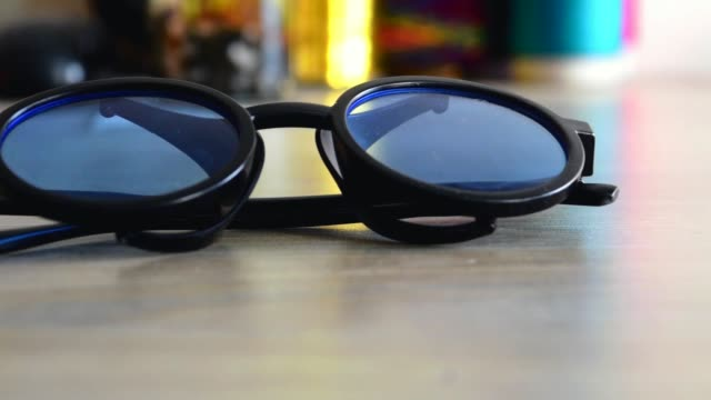 Glasses on the table.  Blue color sunglasses slider view.   Amazing sun glass footage through slider.