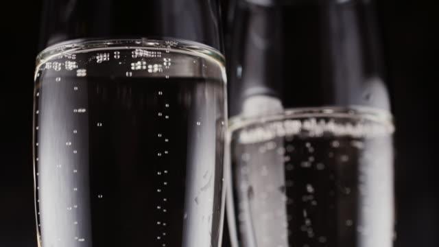 gläser mit champagner bläschen auf dunklem hintergrund - eimer stock-videos und b-roll-filmmaterial