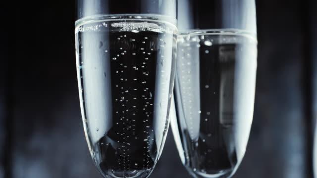 gläser mit champagner bläschen auf dunklem hintergrund - champagner toasts stock-videos und b-roll-filmmaterial