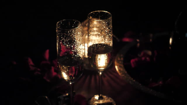 Glasses with champagne, burning candle, rose petals