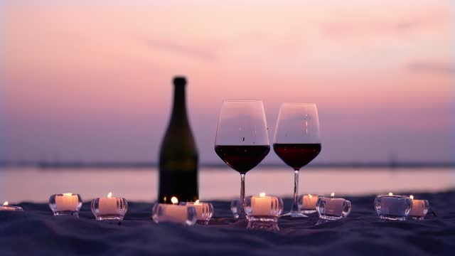 Glasses with red wine and small candles on evening beach