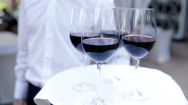 Glasses with wine on a tray. Meeting with guests. video
