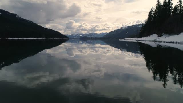 vidéos et rushes de plan d'eau lac alpin miroitant cloud miroir drone faible angle - nord