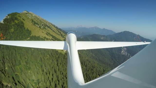 ld-segelflugzeug schleifen in den sonnigen himmel über die üppig grüne landschaft zu tun - fülle stock-videos und b-roll-filmmaterial