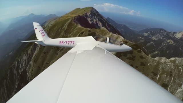 vidéos et rushes de ld planeur volant au-dessus d'une crête de montagne verte au soleil - glisser
