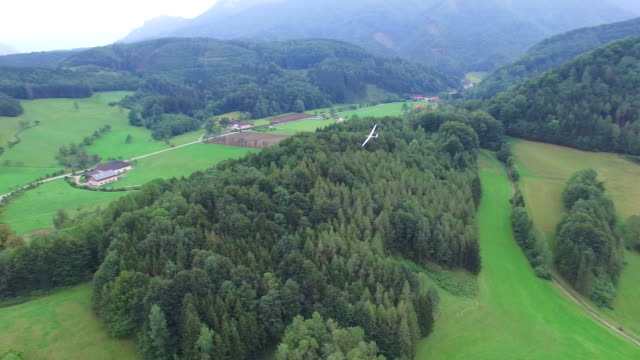 A glider flying over Alps forest, aerial view