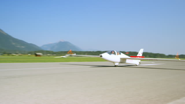 Glider landing on the sunny airstrip