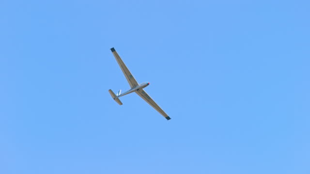 Glider plane moving across the blue sky