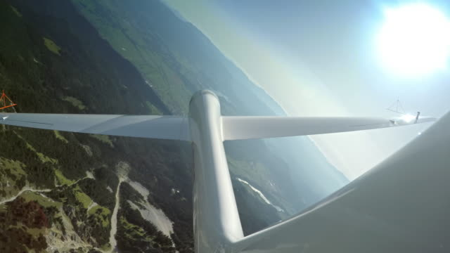 LD Glider sailing above a green mountain ridge on a sunny day