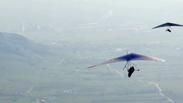 glider taking off the mountain, tracking shot - парапланеризм стоковые видео и кадры b-roll