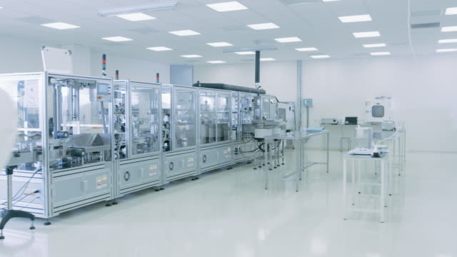 Gliding Shot through Sterile High Precision Manufacturing Laboratory where Scientists in Protective Coverall's Use Computers and Microscopes, doing Pharmaceutics, Biotechnology and Semiconductor Research.