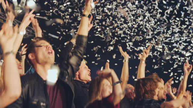 Glitter at concert Crowd dancing and cheering at a concert while glitter is falling from above.   cheering stock videos & royalty-free footage