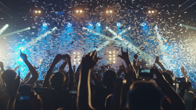 Glitter at concert Crowd dancing and cheering at a concert while glitter is falling from above.   rock music stock videos & royalty-free footage