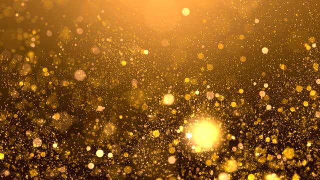 vídeos de stock, filmes e b-roll de faísca dourada de brilho que voa em um fundo borrado - feriado evento