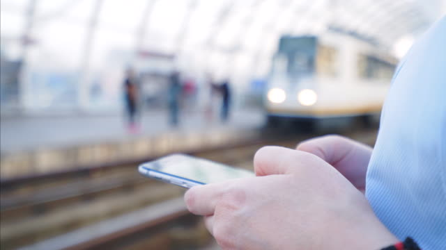 Global communication has never been so easy! Woman using a smart phone while waiting the train. She is always using public transportation to save time and to protect the environment. railroad station platform stock videos & royalty-free footage