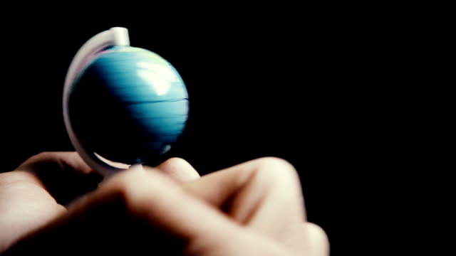 globe and a finger that turn it in high contrast video