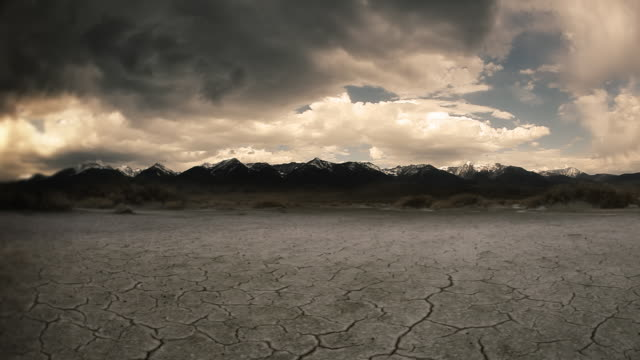 Gloomy dry cracked lake bed in front of mountain video