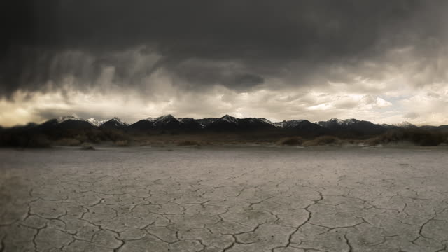 Gloomy storm, cracked lake bed in front of mountain  background. video