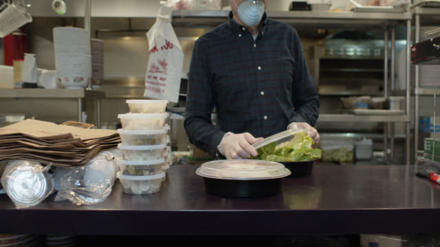 vídeos de stock e filmes b-roll de gloved and masked restaurant owner boxing up food for take out during covid-19 outbreak - covid restaurant