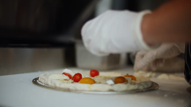 Gloved Chef Spreading Cherry Tomatoes on Pizza