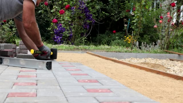 A gloved craftsman is laying concrete tiles using a bubble level and a rubber mallet. Tile laying sounds. Brick walkway paved with professional paver. Laying gray concrete paving slabs in the courtyard of the house on gravelly sandy base.