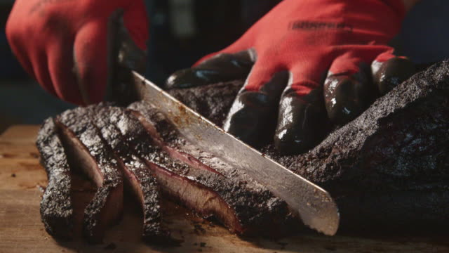 vídeos de stock e filmes b-roll de gloved hands slowly cutting perfectly cooked texas barbecue style beef brisket on a rustic cutting board - churrascada