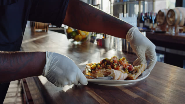 Gloved Server Placing Ceviche on Table video