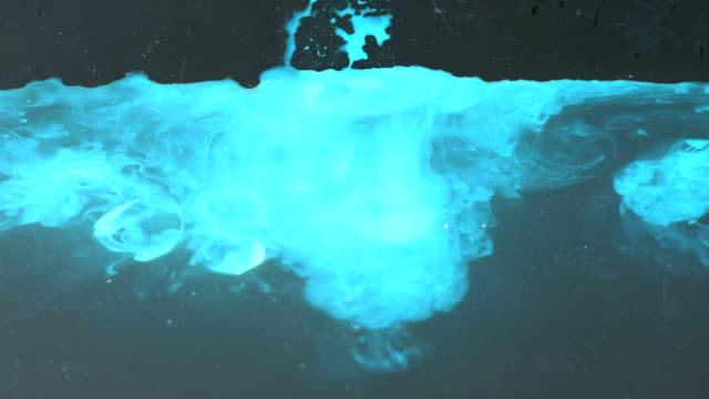 glowing bluish colored ink in water video