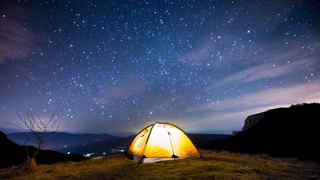 Glowing camping tent in the mountains under the twinkling starry sky. Cinemagraph.