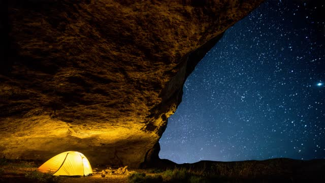 Glowing camping tent in the night grotto under a twinkling starry sky. Cinemagraph