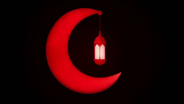 glowing celebration lantern hanging in moon on dark background. ramadan kareem islamic motion background. 3d loopable animation. - фанус стоковые видео и кадры b-roll