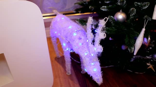 glowing christmas deer near a christmas tree. - poroże filmów i materiałów b-roll