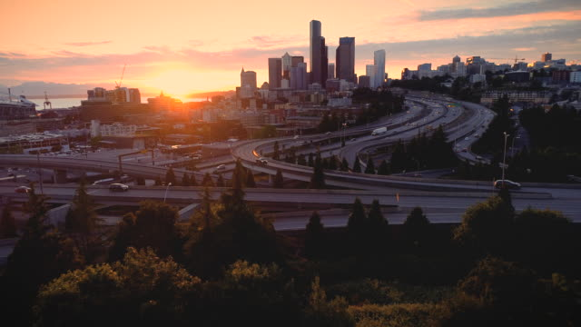Glowing City Skyline Sunset of People Driving Aerial Orange sunlight glow flying with Seattle Washington buildings seattle stock videos & royalty-free footage