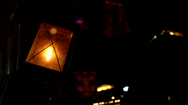 Glowing Flickering Lantern outside store window in urban downtown city at night video