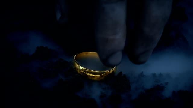 vidéos et rushes de anneau d'or rougeoyant est ramassé du sol - charmeur