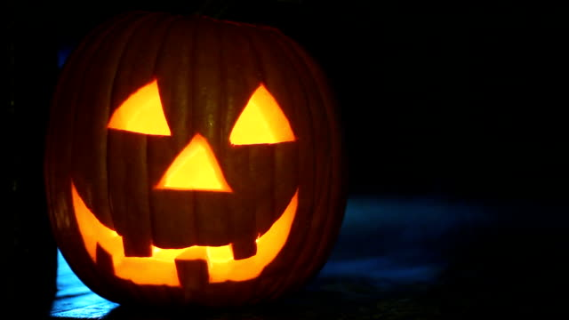 Glowing jack-o-lantern on porch with eerie smoke, ready for Halloween