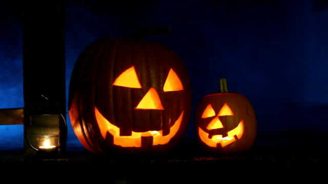 Glowing jack-o-lanterns and candle on porch with eerie smoke behind video