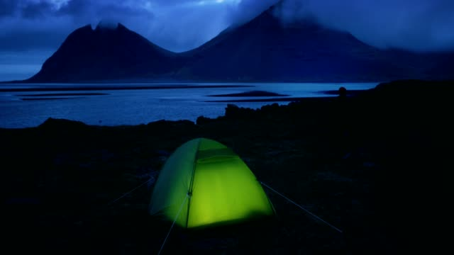 Glowing tent under a cloudy sky