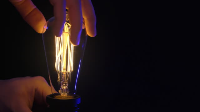 glowing vintage light bulb on black background. turning the lamp on and off. flickering light bulb - stile del xix secolo video stock e b–roll