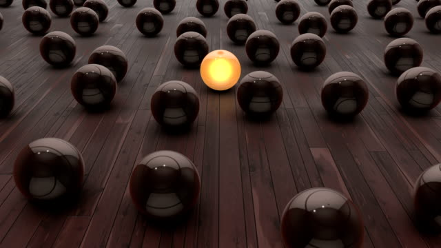 Glowing Yellow Sphere Among Others Orange spheres slowly moving with countless metallic spheres on a wooden reflective floor. Composition describes Standing Out From The Crowd saying. High quality render, banding free, minimum compression for highest quality. individuality stock videos & royalty-free footage