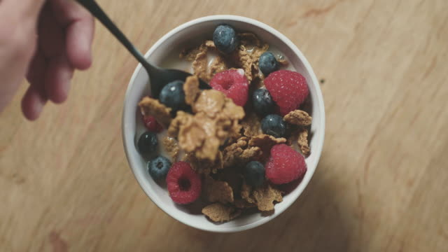 Gluten Free Cereal for Breakfast Gluten free cereal in a white bowl on the kitchen table for breakfast. Seen from directly above. cereal stock videos & royalty-free footage