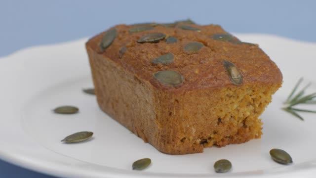 açık mavi arka planda ayarlanmış beyaz plaka kabak tohumu ile gluten ücretsiz kabak ekmek. - kek dilimi stok videoları ve detay görüntü çekimi