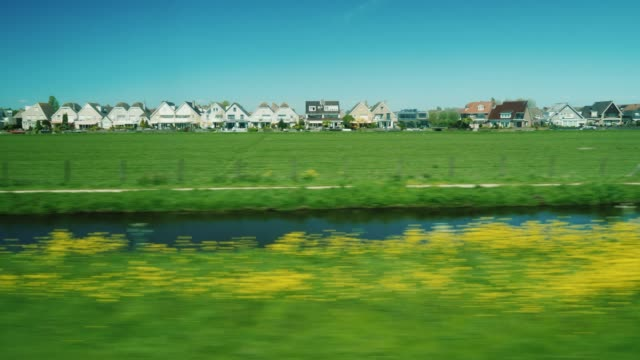 Go along the scenic terrain in the Netherlands. Ancient wooden houses, meadows and a canal seen from the window video