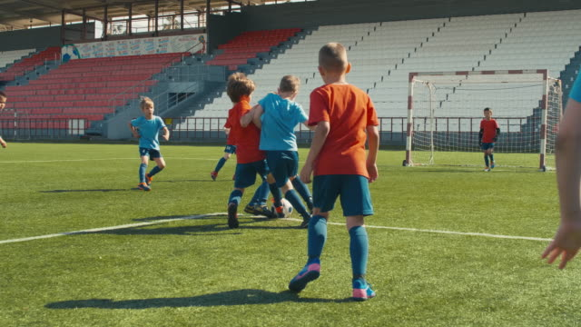 Goal in kid soccer game Children playing soccer on arena, attacking and making goal goal post stock videos & royalty-free footage