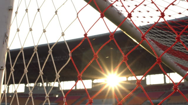 vídeos de stock e filmes b-roll de goal with sunlight and stadium backgground 4k - campeão soccer football azul
