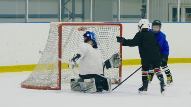 Goalie missing puck in child hockey match Panning shot of goalie in youth hockey match trying to save his post but conceding a goal goal post stock videos & royalty-free footage
